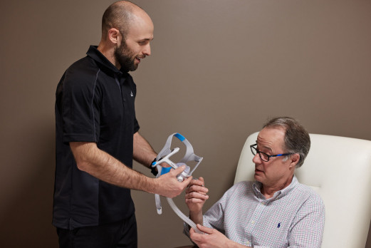 a health specialist who explains to his patient the treatment for sleep apnea